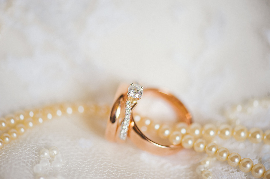 wedding bands and engagement ring laying on lace with ivory pearl necklace
