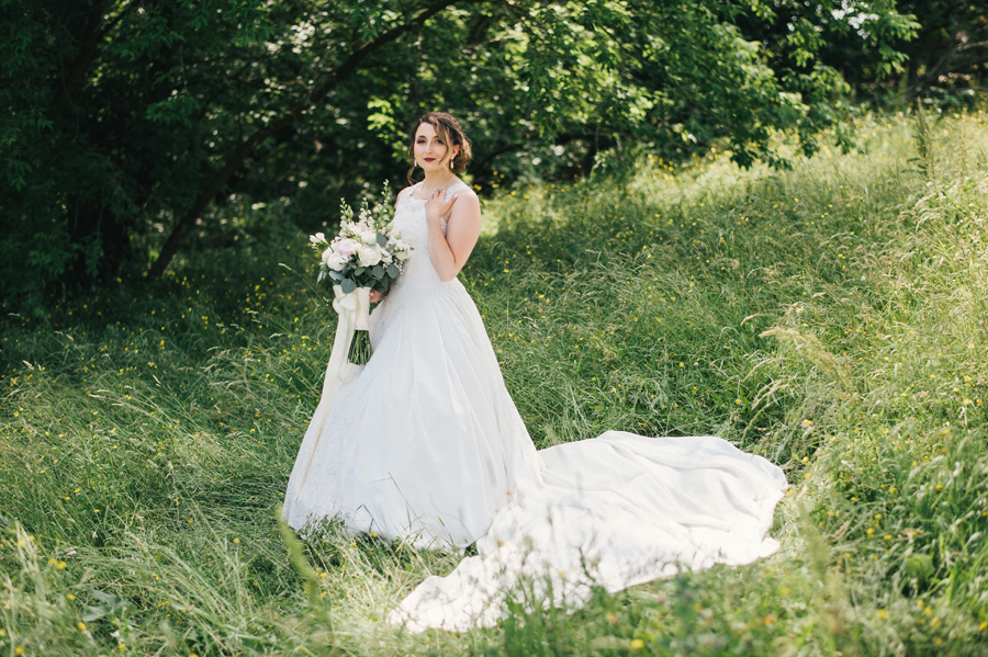 full length shot of bride in a field holding bouquet made by lipinoga florist