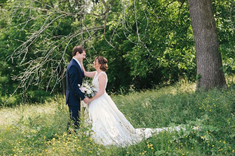 bride and groom gazing at each other in a field
