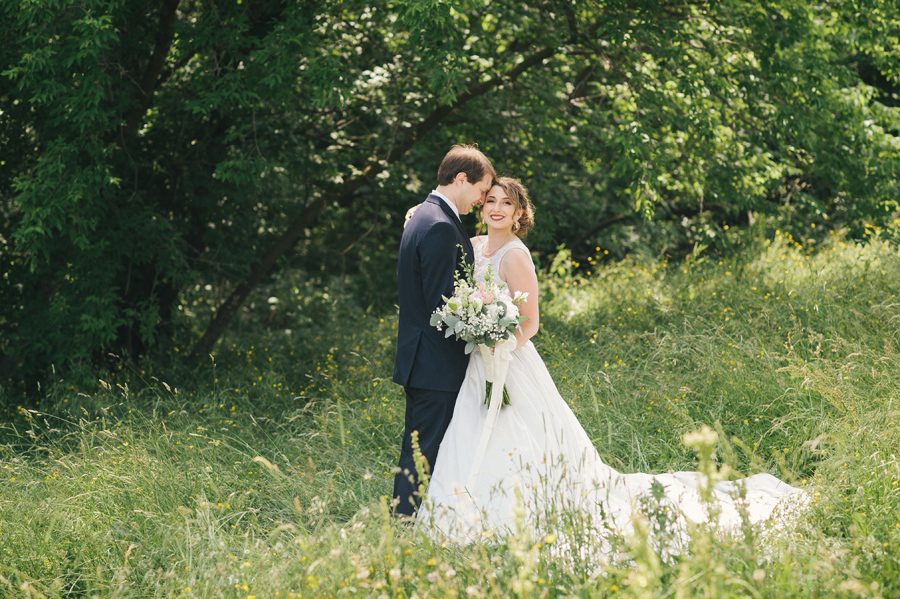 bride and groom posing near a wooded area