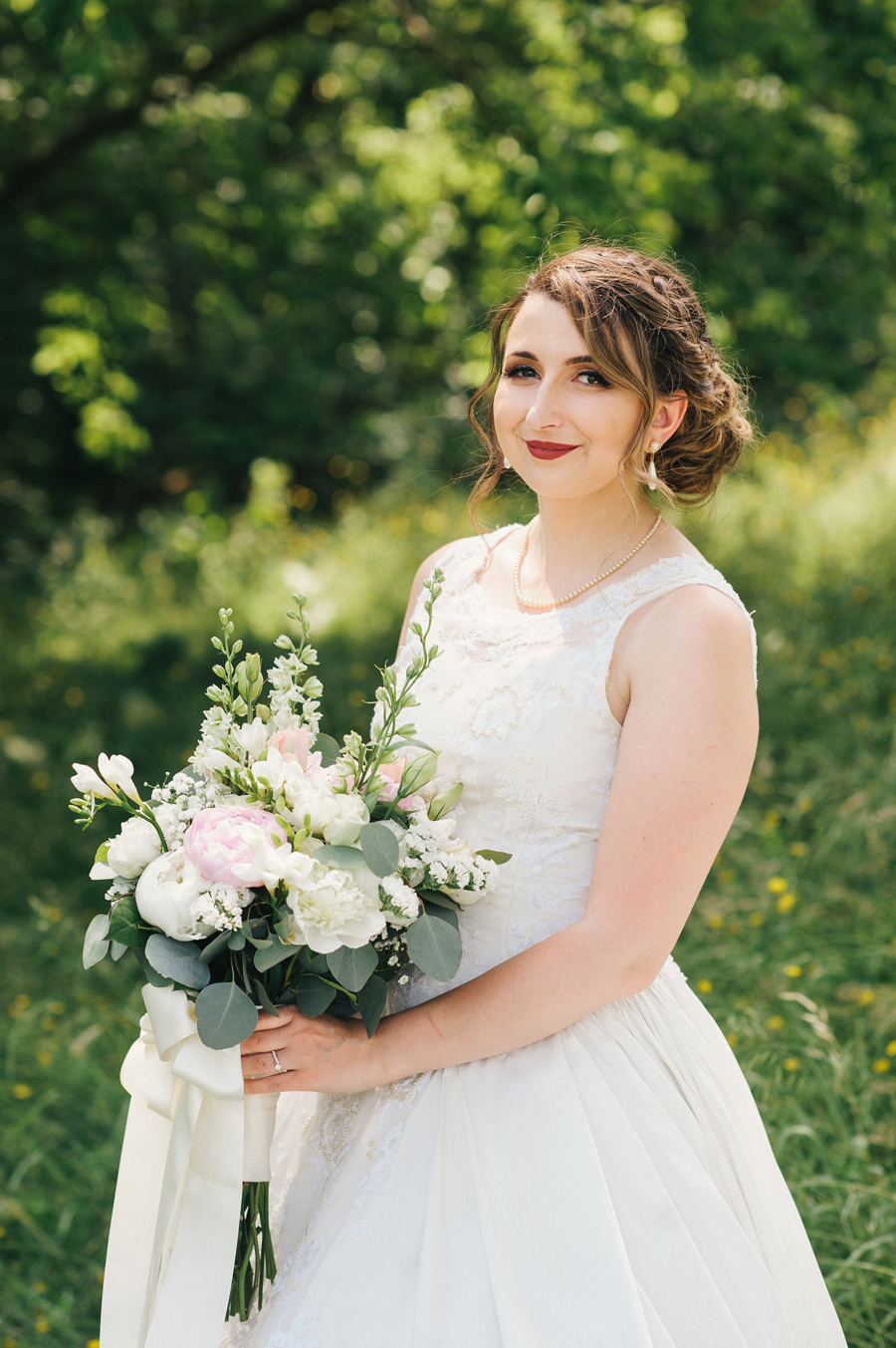 bride smiling and posing with her bouquet of white and light pink flowers