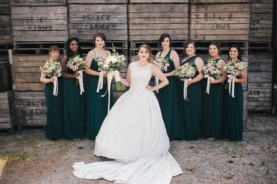 bride looking sassy with bridal party in front of crates at becker farms