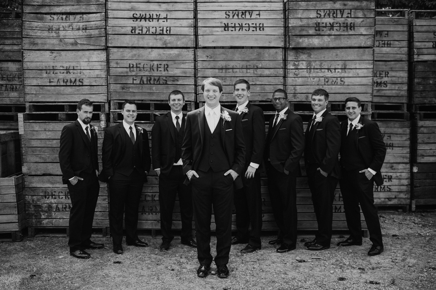 black and white of groom and groomsmen in front of wooden palettes at becker farms