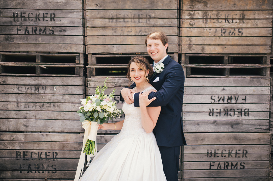 groom wrapping arms around bride in front of wooden crates becker farms