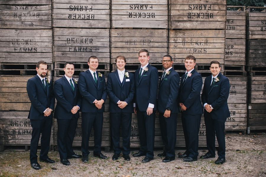 groomsmen lined up in front of becker farms wood palette wall