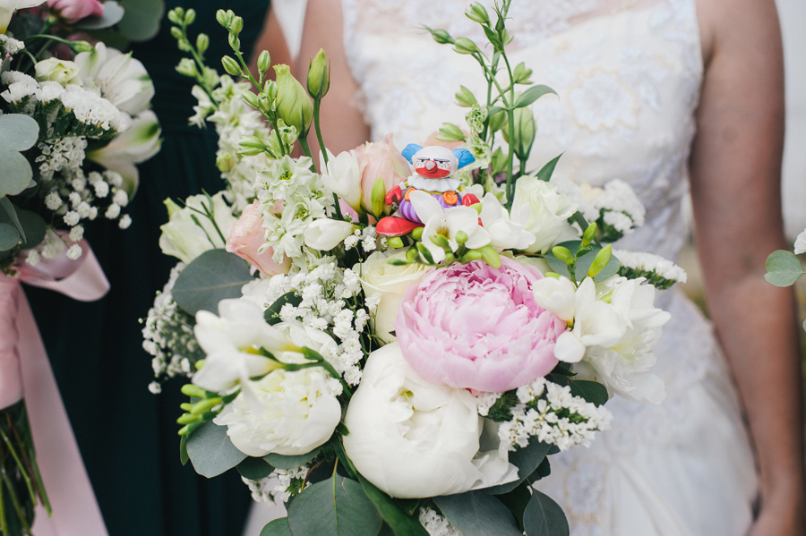 close up of small clown toy resting on bride's bouquet