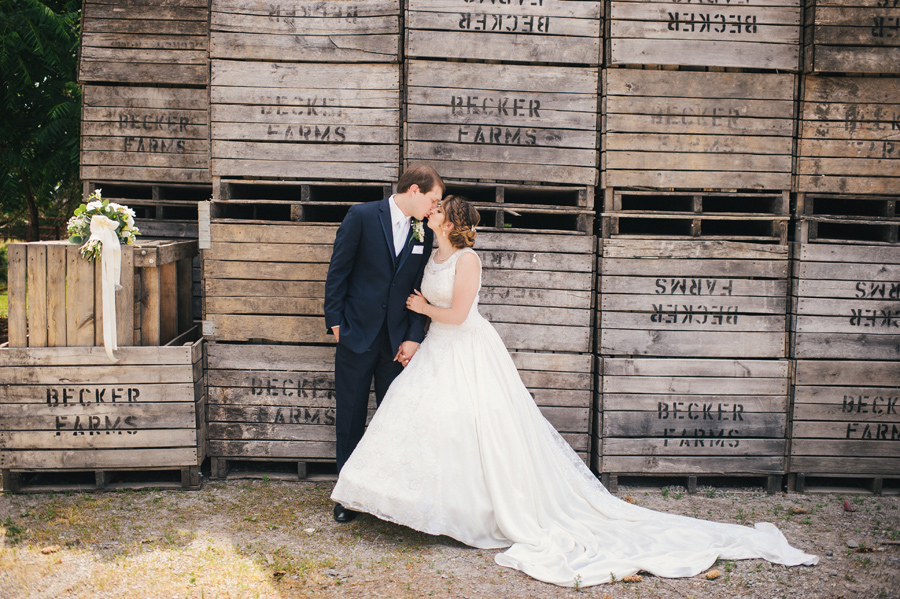 bride and groom kissing in front of wooden crate wall at becker farms