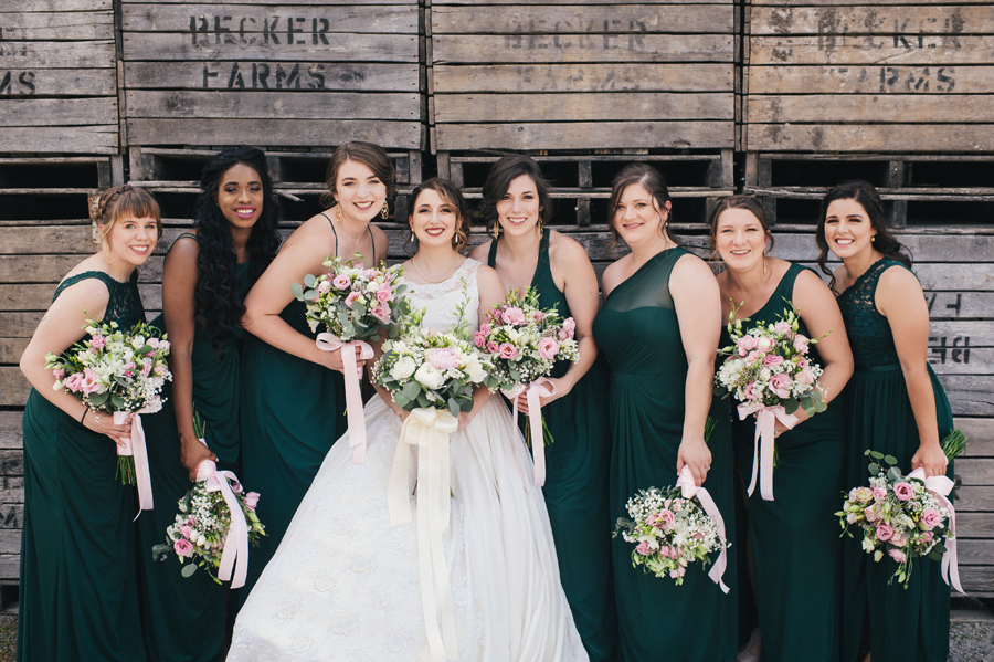 bride and bridesmaids smiling with wooden crates in background