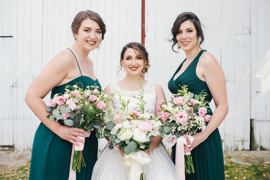 bride and 2 bridesmaids smiling and holding bouquets