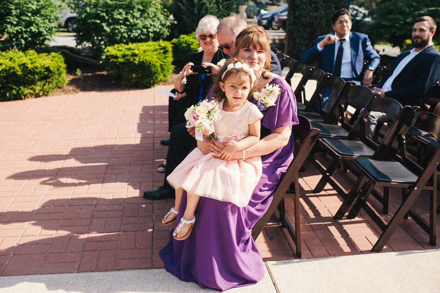 a flower girl sitting on a wedding guest's lap