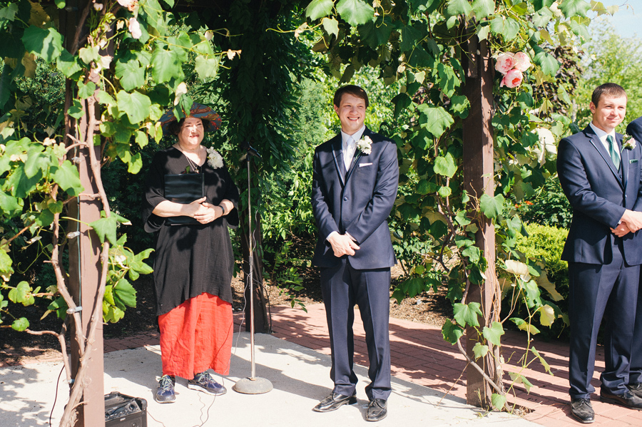 groom awaiting his bride under the grapevine arbor