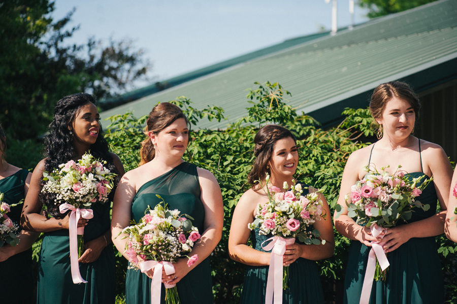 bridesmaids looking on while holding bouquets of white and pink flowers