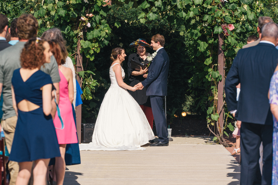 bride and groom facing each other under a grapevine arbor