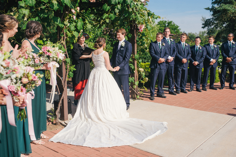 bride and groom holding hands under a grapevine arbor at becker farms