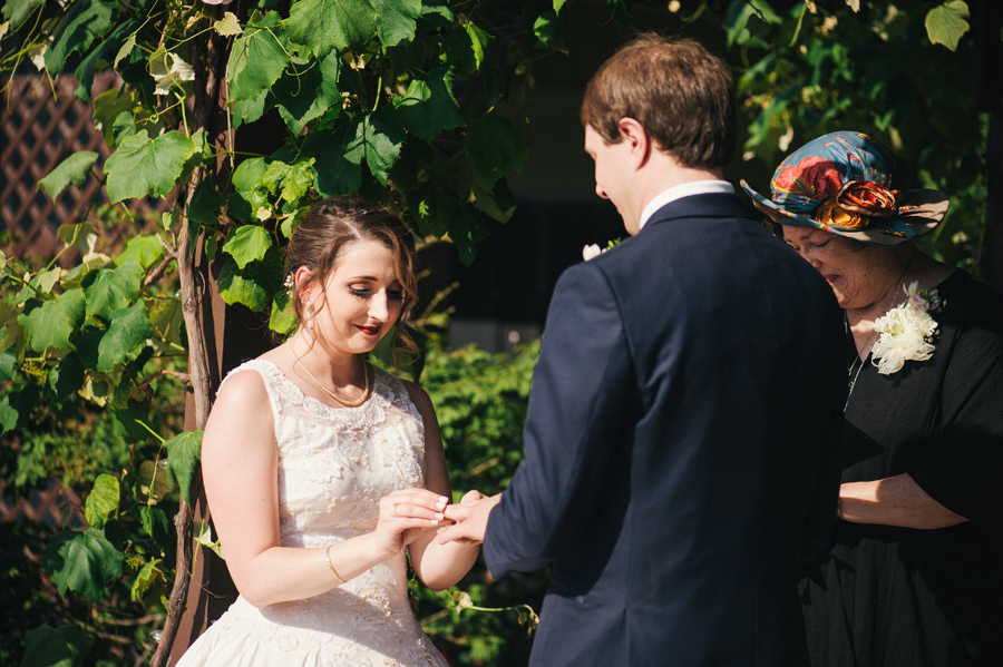 bride placing a wedding band on groom's finger