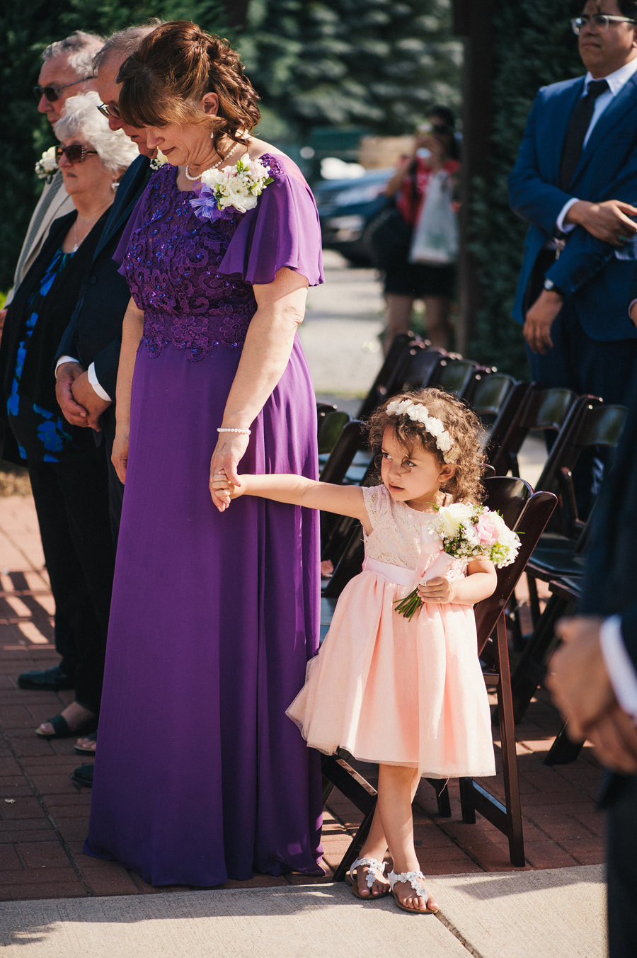 flower standing and holding a wedding guest's hand