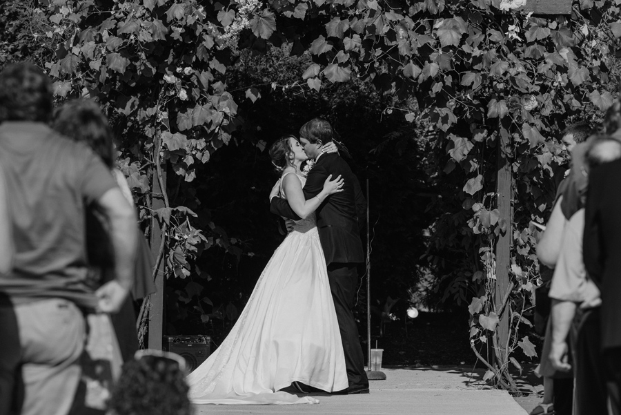 black and white of bride and groom kissing at the end of the wedding ceremony