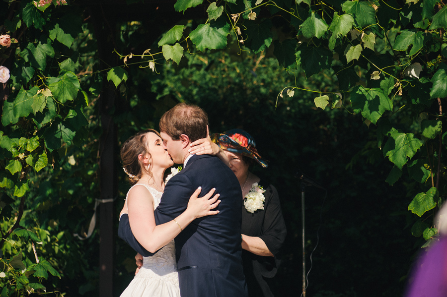 bride and groom kissing under grapevine arbor at becker farms