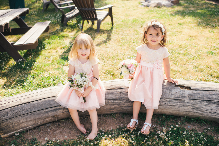 two flower girls sitting on a log with bouquets and light pink dresses
