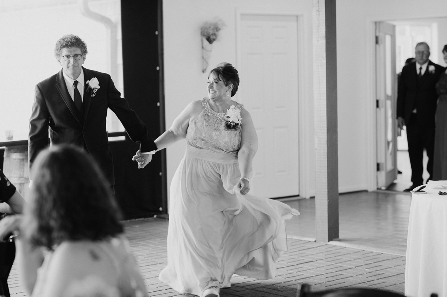 black and white of bride's parents entering reception