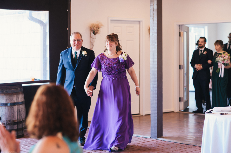groom's parent's entering reception party hand in hand