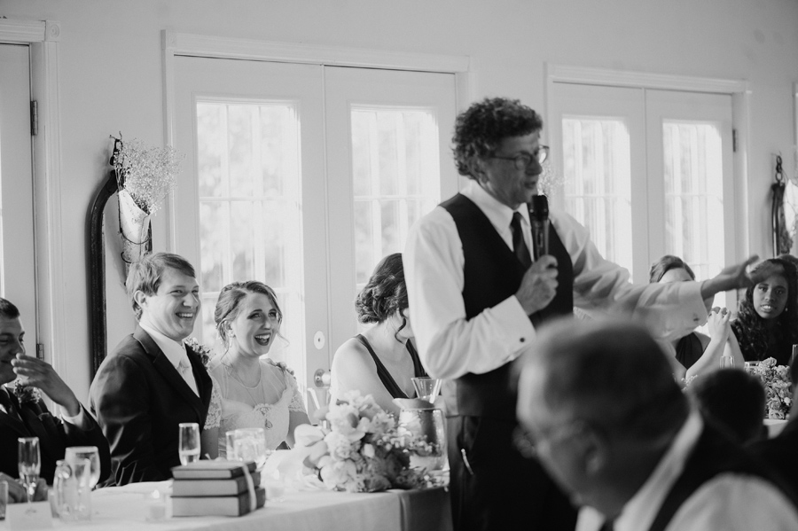 black and white of bride and groom laughing during father of the bride's speech