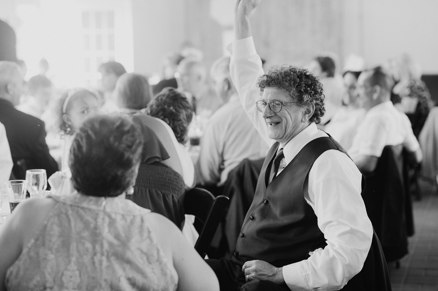 black and white of father of the bride cheering during reception