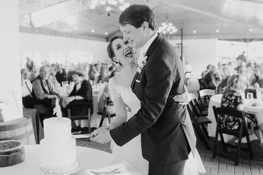 black and white of bride and groom performing cake cutting ceremony