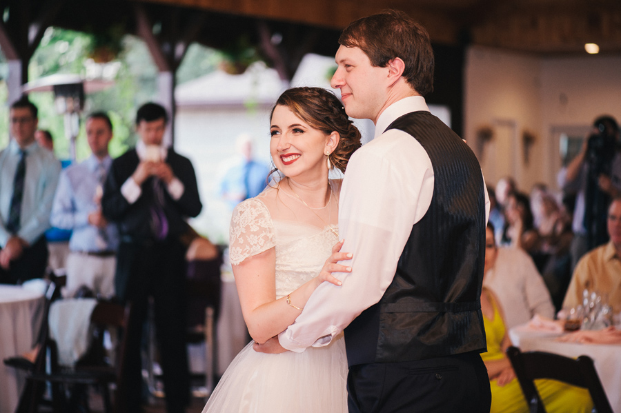 bride and groom smiling at guests during first dance