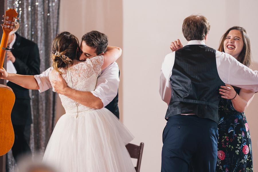 bride and groom hugging reception musicians