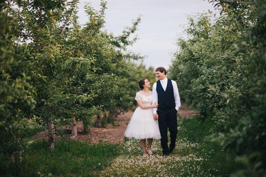 bride and groom walking between rows of apple trees at becker farms