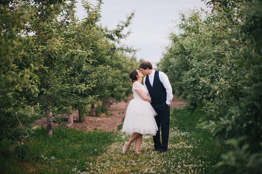 bride and groom kissing in center of apple orchard
