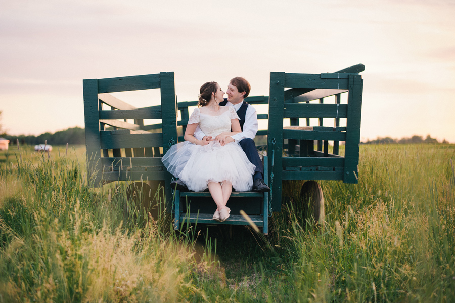 bride and groom sitting on wooden trailer in a field