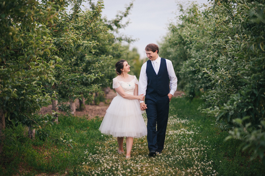 bride and groom strolling hand in hand through apple trees