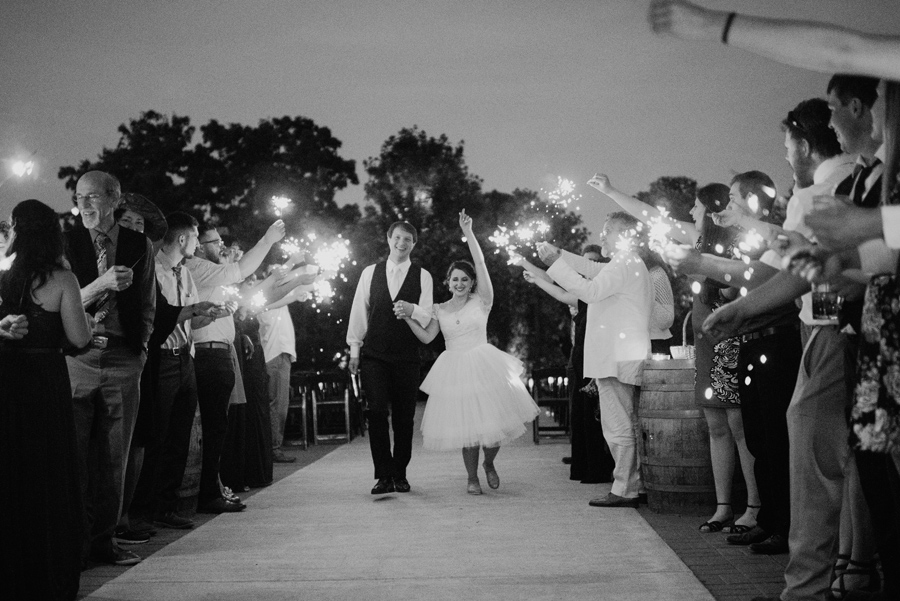 black and white of bride and groom walking through sparkler send off