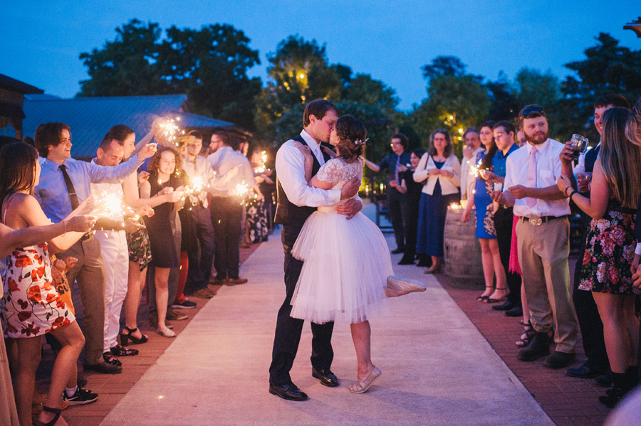 bride and groom kissing during sparkler send off at night