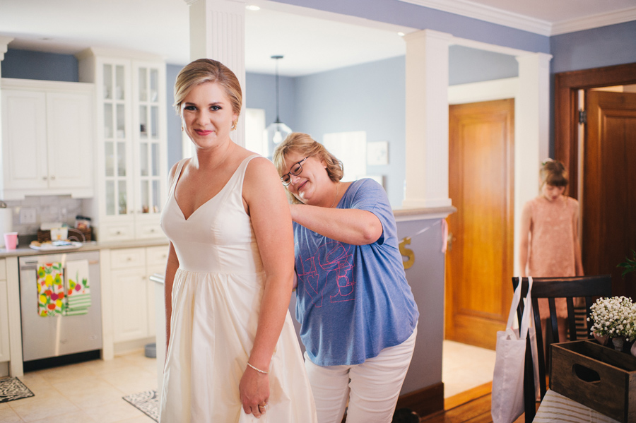 mother of the bride buttoning bride's dress