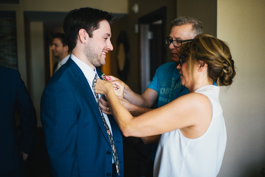 mother and father of the groom pinning boutonniere