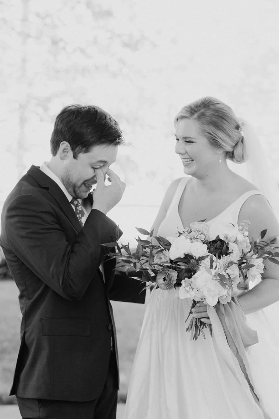 black and white photo of groom crying during first look