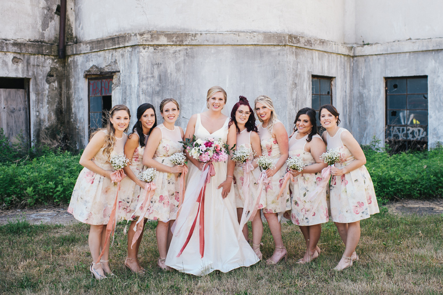 bride with bridal party in short pink floral dresses
