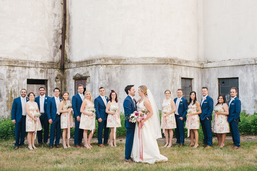 bridal party lined up in front of grain silos