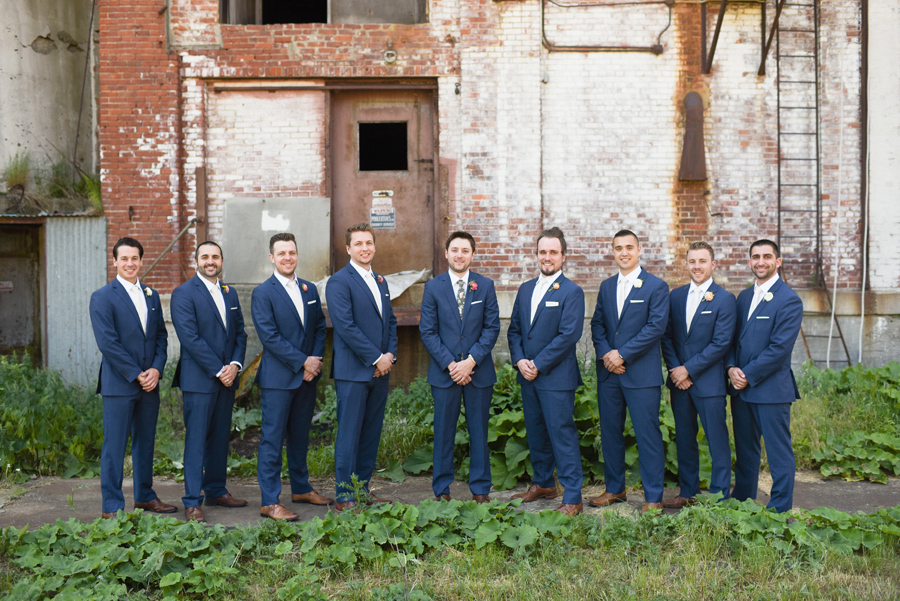 groomsmen lined up in front of brick wall
