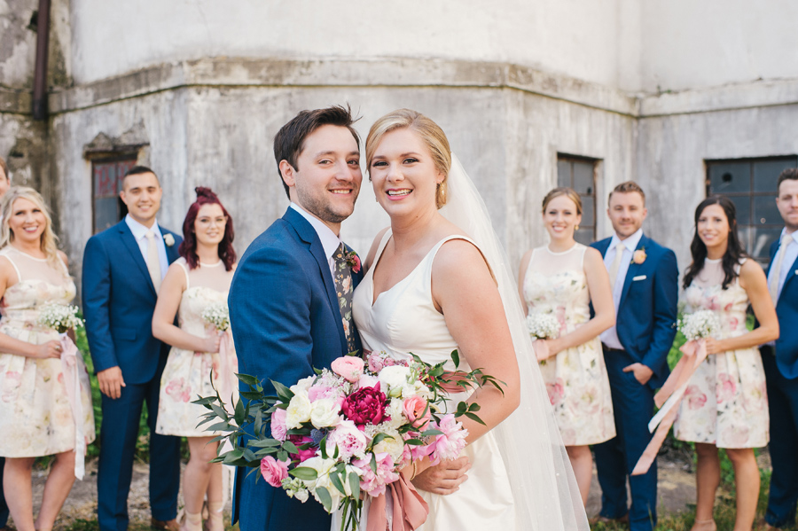bride and groom smiling in front of silo city