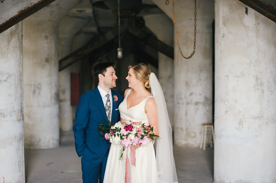 bride and groom smiling at each other inside silo city