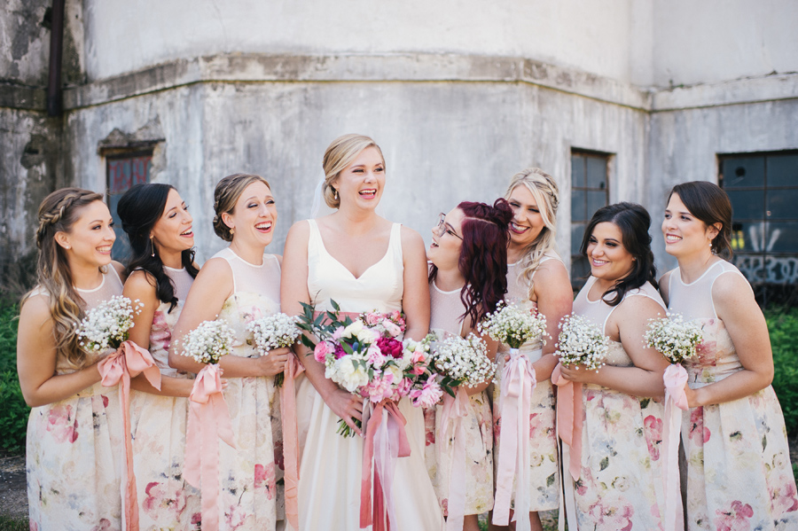bride and bridesmaids laughing with each other at silo city