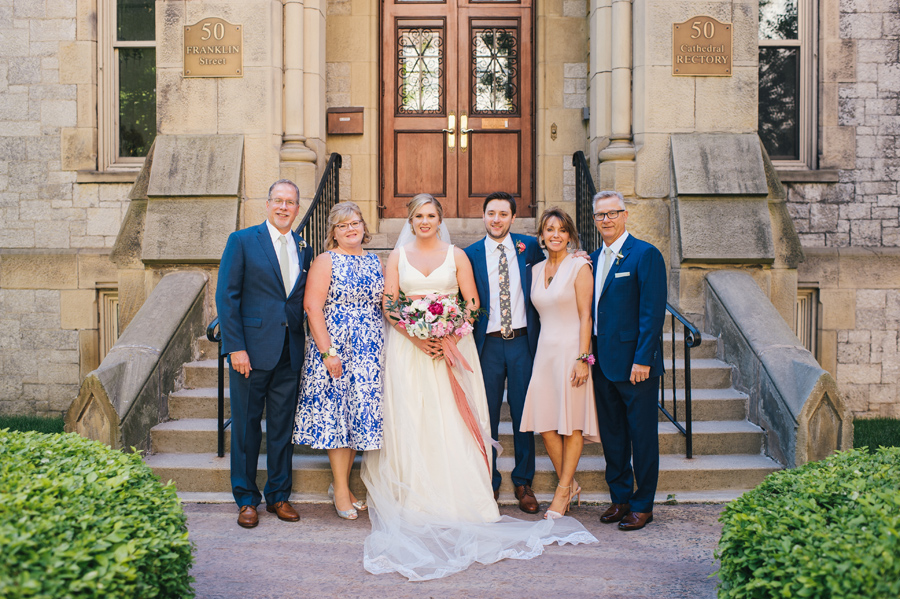 bride and groom with their parents in front of st joseph cathedral