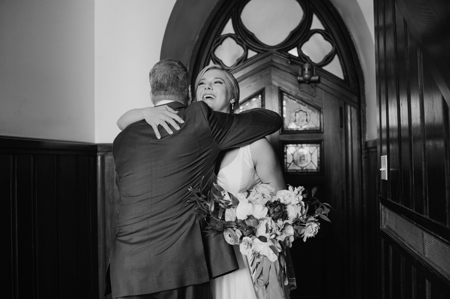 black and white of bride hugging her father inside the church