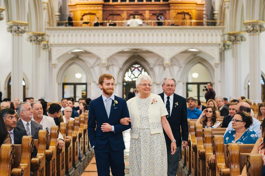 groomsmen escorting grandmother down the aisle