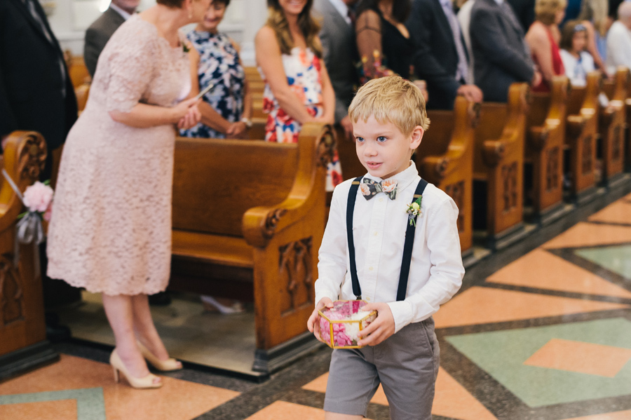 ring bearer wearing floral print bow tie walking down the aisle