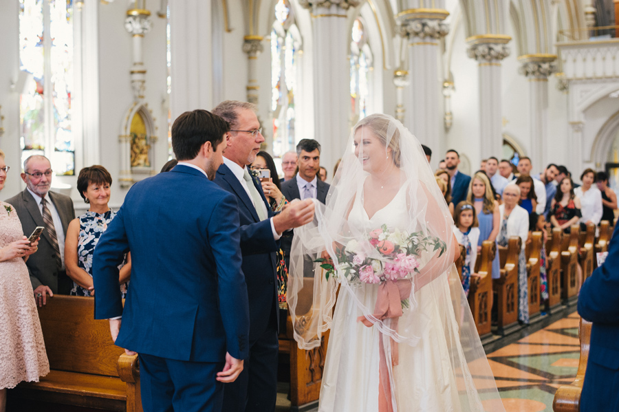 father of the bride lifting her veil